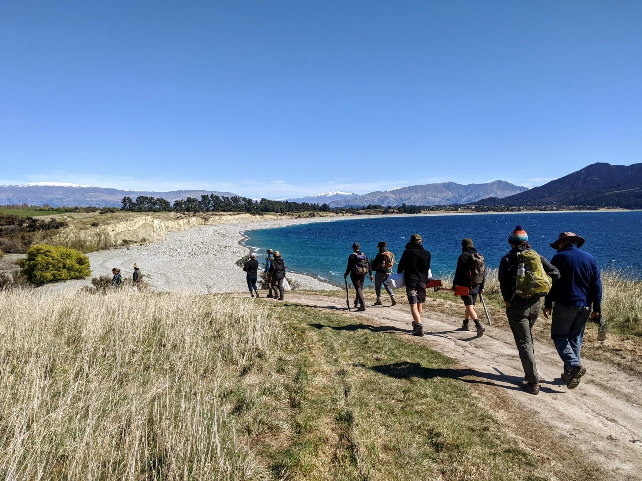 Partnering to Plant team walking to their planting site along Lake Hāwea