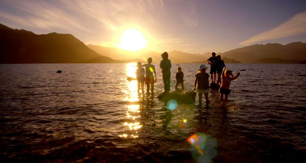 Kids in the lake at sunset